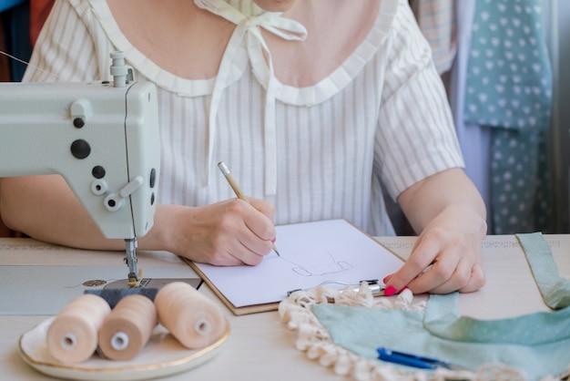 Mãos femininas do estilista desenhando o esboço do novo vestido da moda