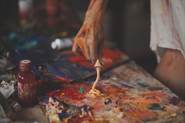 Mãos femininas do pintor com pincéis, tintas e uma paleta para desenhar
