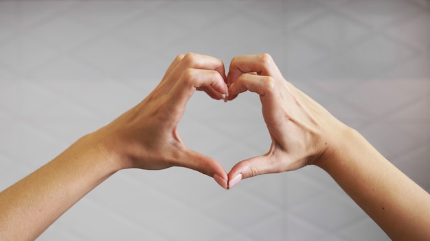 Mãos femininas dobradas em forma de coração em um branco borrado dentro de casa