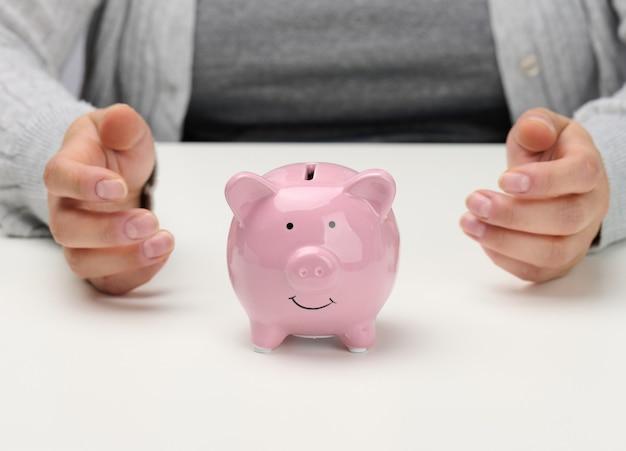 Mãos femininas e cofrinho de cerâmica rosa. conceito de acumulação, controle de orçamento