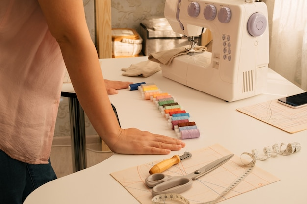 Mãos femininas e fios no local de trabalho, conceito de costura