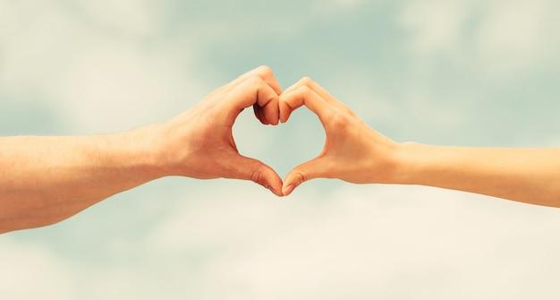 Mãos femininas e masculinas em forma de coração contra o céu. mãos em forma de coração de amor. coração de mãos em um céu.