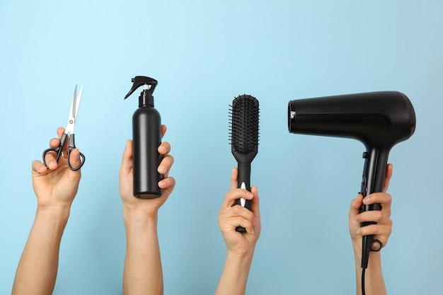 Mãos femininas e masculinas seguram ferramentas de cabeleireiro em azul