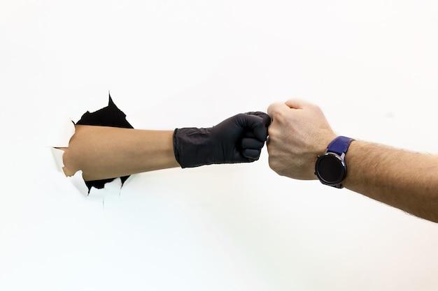 Mãos femininas e masculinas, uma em uma luva protetora e a outra sem uma luva