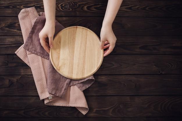 Mãos femininas e pratos de madeira na velha mesa de madeira