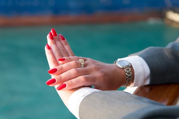 Mãos femininas e relógio de pulso com manicure vermelha e anel de ouro no dedo com diamantes perto da água