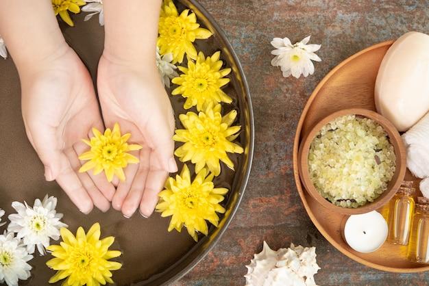 Mãos femininas e tigela de água do spa com flores, close-up. spa de mãos.