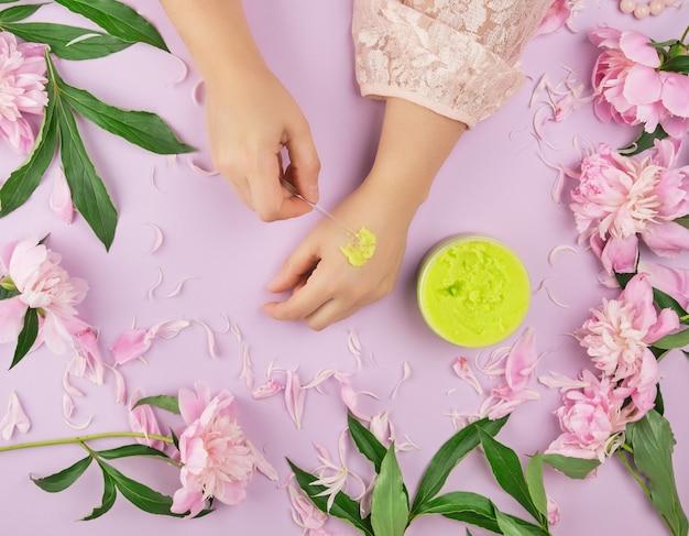Mãos femininas e um frasco com esfoliante verde espesso e peônias de floração rosa
