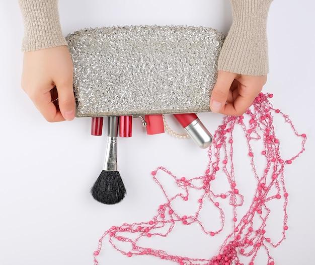 Mãos femininas e um saco cosmético prata com cosméticos em um fundo branco