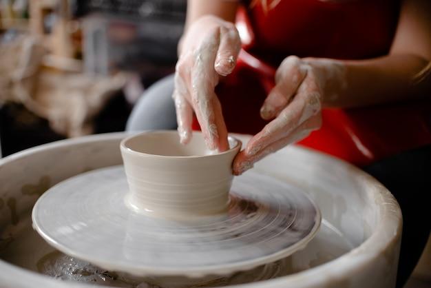 Mãos femininas elaborando um copo de cerâmica em uma roda de oleiro.