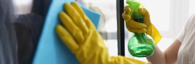 Mãos femininas em luvas amarelas lavam as janelas com pano e agente de limpeza
