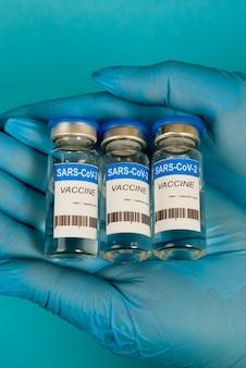 Mãos femininas em luvas azuis segurando frascos da vacina contra o coronavírus covid-19. fechar-se.