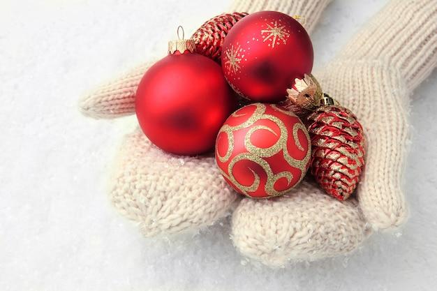 Mãos femininas em luvas, bolas de árvore de natal, na cor de fundo
