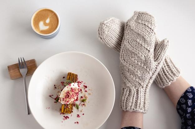 Mãos femininas em luvas brancas com bolo e café na mesa branca com bolo. conceito de inverno, calor, feriados, eventos.