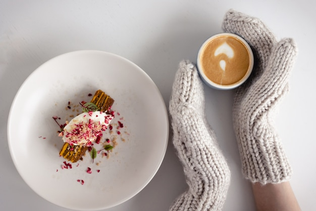 Mãos femininas em luvas brancas segurar a xícara de café quente com espuma na mesa branca com bolo. fundo de natal. conceito de inverno, calor, feriados, eventos. foco suave. vista do topo.