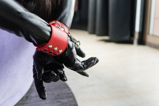 Mãos femininas em luvas de couro e algemas vermelhas