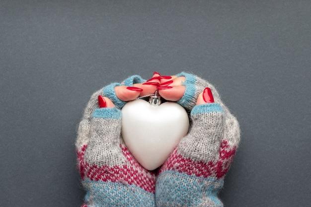 Mãos femininas em luvas de malha, com coração fosco e unhas vermelhas brilhantes