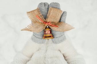 Mãos femininas em luvas de malha com um sino ornamental para decoração de Natal