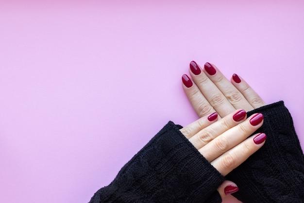 Mãos femininas em luvas de malha pretas com uma bela manicure brilhante - unhas cor de vinho, vermelho escuro em um fundo rosa com espaço de cópia