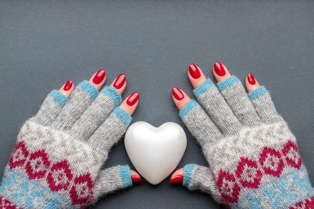 Mãos femininas em luvas de malha quentes, com coração e unhas vermelhas brilhantes na parede cinza