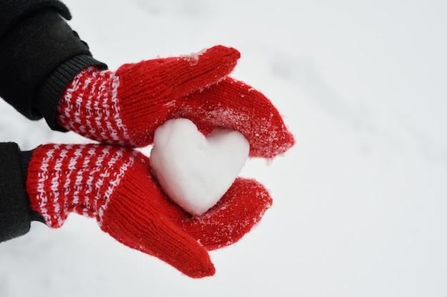 Mãos femininas em luvas de malha vermelhas quentes com coração nevado