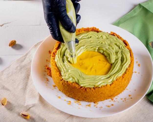 Mãos femininas em luvas decorando cheesecake com creme de pistache na cozinha