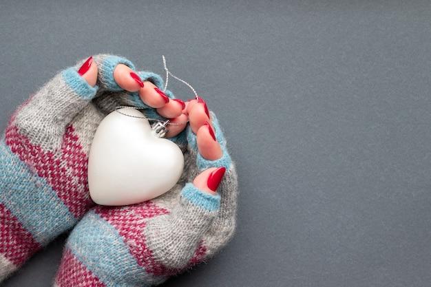 Mãos femininas em luvas quentes, com coração e unhas vermelhas brilhantes na parede cinza