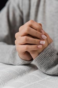 Mãos femininas em posição de oração com a bíblia