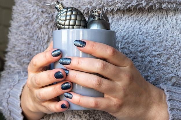 Mãos femininas em suéter cinza fofo de malha com linda manicure