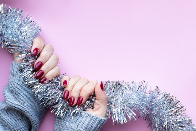 Mãos femininas em suéter de malha cinza com manicure brilhante