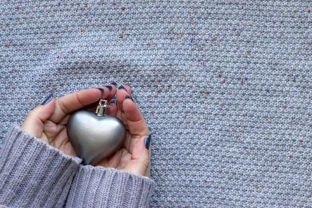 Mãos femininas em suéter de malha com coração e unhas brilhantes azuis na parede de malha