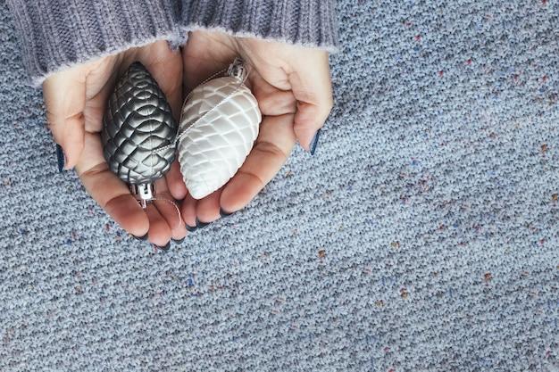 Mãos femininas em suéter de malha com pinhas de árvore de natal e uma bela manicure