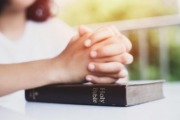 Mãos femininas em uma bíblia sagrada