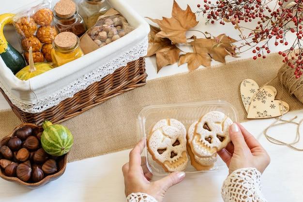 Mãos femininas embalando biscoitos com caveira de halloween