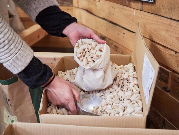 Mãos femininas, enchendo o saco de pano com macarrão cru, comprando a granel