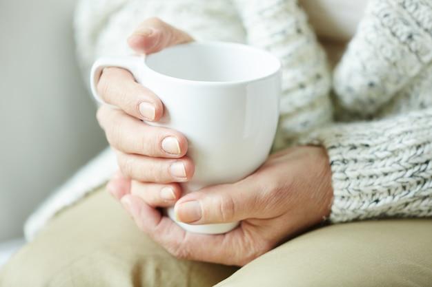 Mãos femininas enrugadas, segurando a xícara de café