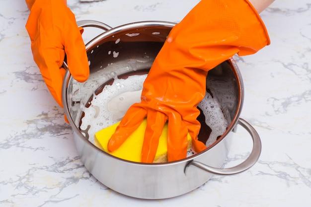 Mãos femininas ensaboam a panela com uma esponja para lavar a louça em cima da mesa