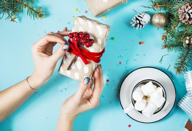 Mãos femininas envolvendo a caixa de presente de natal acima da mesa azul.