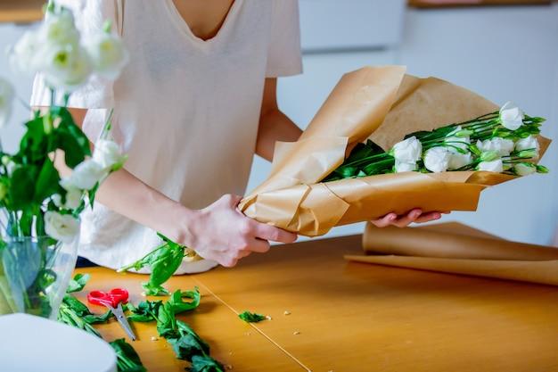 Mãos femininas envolvendo um rosas brancas e papel