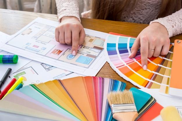 Mãos femininas escolhendo a cor das paredes do quarto