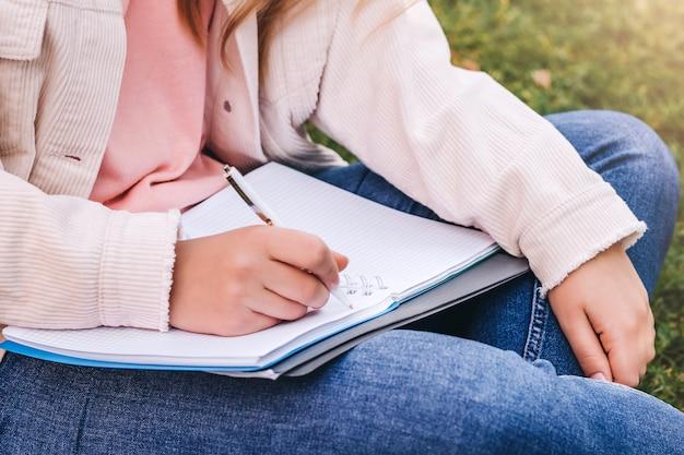 Mãos femininas escrevem em um caderno.