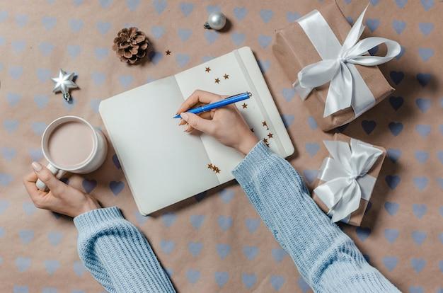 Mãos femininas, escrevendo a lista de desejos no notebook perto de presentes