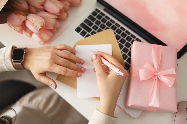 Mãos femininas escrevendo desejos no último papel para o dia dos namorados ou aniversário com caixa de presente e laptop na mesa, vista superior.