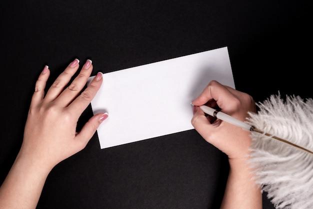 Mãos femininas, escrevendo em papel branco com caneta vitage de penas com copyspace