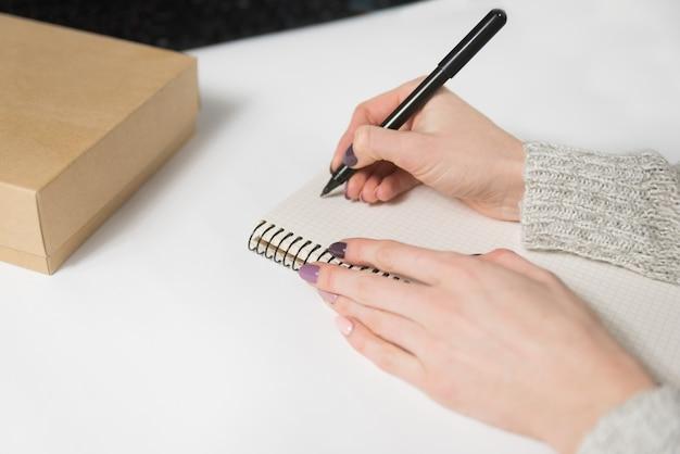 Mãos femininas, escrevendo em um caderno em branco.