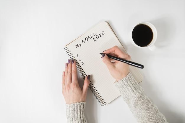 Mãos femininas escrevendo meus objetivos em um caderno.