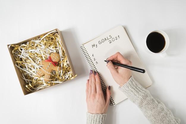 Mãos femininas escrevendo my goals 2021 em um caderno. caneca de café e homem-biscoito, vista superior.