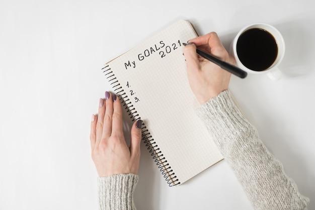 Mãos femininas escrevendo my goals 2021 em um caderno. caneca de café na mesa, vista superior.