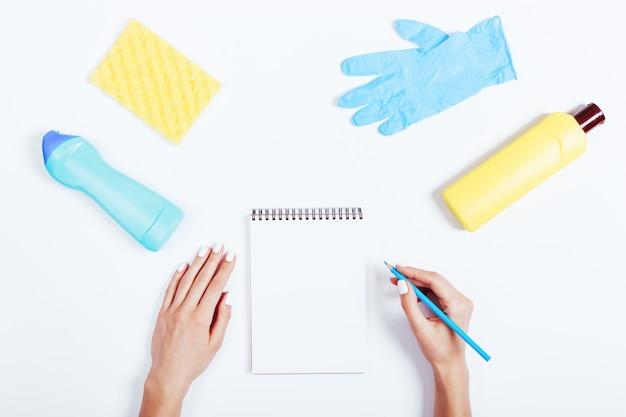 Mãos femininas, escrevendo no bloco de notas, amarela e azul garrafa de detergente e esponja na superfície branca