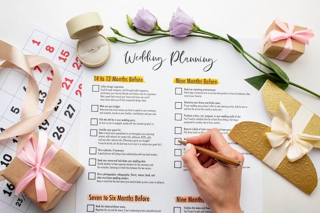 Mãos femininas escrevendo no planejador de casamento